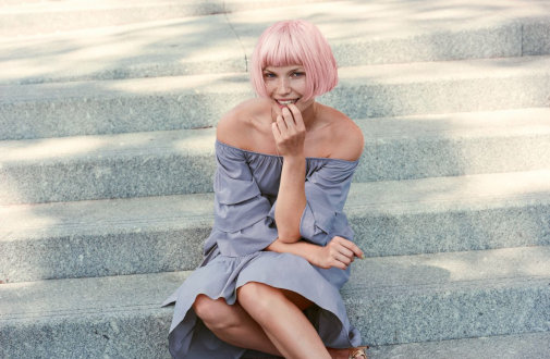A woman model for Keune hair products with pink hair styled in a pageboy cut sits on concrete steps.